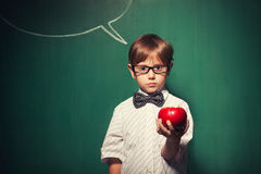 Little boy with glasses standing in front of chalkboard with com Stock Photo