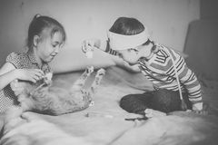 Little boy in the glasses with syndrome dawn and blonde girl play with toys and ginger cat. Black and white.  royalty free stock image