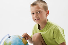 Little boy with globe. Looking at camera Royalty Free Stock Photography