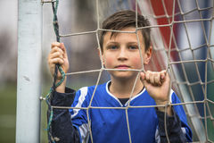 Little boy in goalkeeper uniform behind mesh football goal on the stadium. Royalty Free Stock Image