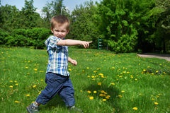 Little boy goes on meadow and indicates direction Stock Photo