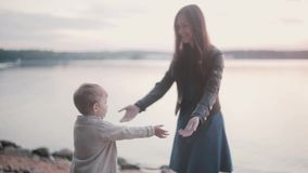 Little boy going through the rocks to mother. Woman waiting son in the distance and supports boy, lending hands. stock footage
