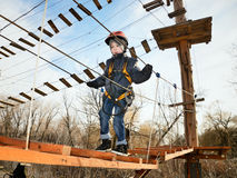 Little boy going on suspension bridge in the equipment and looki Stock Photography