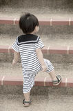 Little boy going up stairs Stock Photo