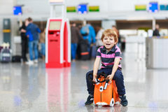Little boy going on vacations trip with suitcase at airport. Beautiful blond boy having fun wiht suitcase at airport, indoors. Going on holidays Royalty Free Stock Images