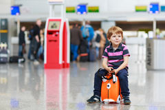 Little boy going on vacations trip with suitcase at airport. Beautiful blond boy having fun wiht suitcase at airport, indoors. Going on holidays Stock Photo