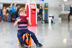 Little boy going on vacations trip with suitcase at airport. Beautiful blond boy having fun wiht suitcase at airport, indoors. Going on holidays. Empty counters Stock Photos