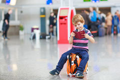 Little boy going on vacations trip with suitcase at airport. Beautiful blond boy having fun wiht suitcase at airport, indoors. Going on holidays. Empty counters Royalty Free Stock Photography