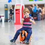 Little boy going on vacations trip with suitcase at airport. Beautiful blond boy having fun wiht suitcase at airport, indoors. Going on holidays. Empty counters Stock Images