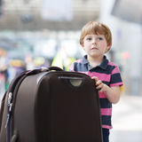 Little boy going on vacations trip with suitcase at airport Stock Images