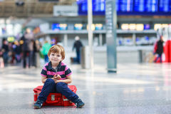 Little boy going on vacations trip with suitcase at airport Stock Photo
