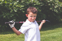 Little boy golfer with driver club over shoulders posing for cam Stock Images