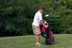 Little boy golfer with his golf bag on the fairway prepares for Royalty Free Stock Photography