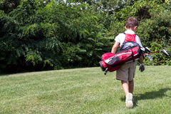 Little boy golfer walking with his golf bag on the fairway Royalty Free Stock Photos