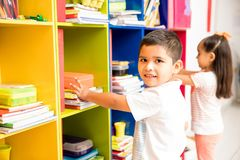 Little boy grabbing some books for preschool Royalty Free Stock Photography