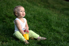 Little boy on a grass. Little boy with pail sits on a green grass royalty free stock photography