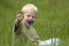 Little boy in the grass. A 2 year old sitting in the grass waving at you stock photo