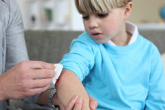 Little boy with grazed elbow. Little boy with a grazed elbow Royalty Free Stock Images