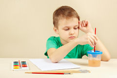 Little boy in green shirt going to paint colors Royalty Free Stock Photo