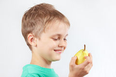 Little boy in a green shirt with juicy yellow pear Royalty Free Stock Photos