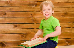 Little boy in green shirt with open book Royalty Free Stock Photo