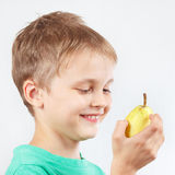 Little boy in green shirt with ripe yellow pear Royalty Free Stock Photos