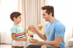 Little boy greeting dad with Father`s Day. Little boy greeting his dad with Father`s Day stock photo