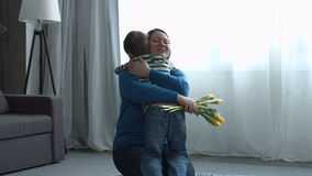 Little boy greeting his mother on Mother`s day. Loving little boy greeting her smiling attractive middle aged mother and giving her yellow tulips flowers on