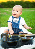 Little boy with a guitar on the grass Royalty Free Stock Photo