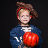 Little boy in halloween costume of pirate posing with pumpkin over black background Stock Photo