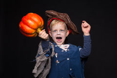 Little boy in halloween costume of pirate posing with pumpkin over black background Royalty Free Stock Photography