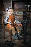 Little boy with hammer imitating the cobbler Royalty Free Stock Image