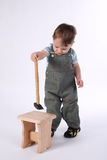Little boy with hammer and wooden chair Stock Image
