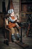 Little boy hammering. Retro shot of a little boy hammering and imitating the cobbler Royalty Free Stock Photography