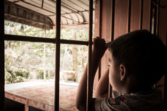 Little boy Hand in jail looking out the window Stock Photography