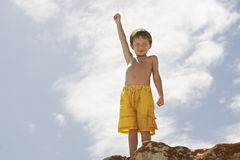 Little Boy With Hand Raised Standing On Rock Royalty Free Stock Photo