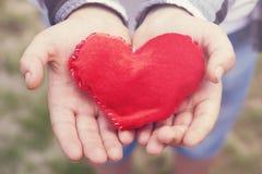 Bright symbol of love in children palms stock photos