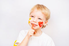 Little boy hands painted in colorful paints. Heart on face stock photos