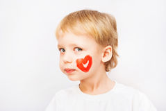 Little boy hands painted in colorful paints. Heart on face stock photography