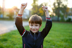 Little boy hands up winning. Outdoor portrait Stock Images