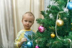 Little boy hanging decorations for Christmas spruce Royalty Free Stock Images