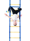 Little boy hanging head down on the bar Royalty Free Stock Image