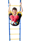 Little boy hanging on sports rings and keeps kicking a red heart. On a white background stock photos
