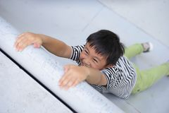 Little boy hanging on wall on hands and trying to climb up.  stock photo
