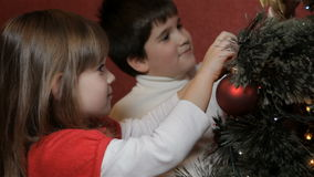 Little boy hangs decorating bow on christmas tree. Little boy hanging decorating bow on christmas tree. Little caucasian boy trying on the golden colored bow on stock video footage