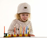 Little boy on Hanukkah. Young blond hair three year old boy lighting the candles in the Jewish tradition to celebrate Hanukkah Stock Images