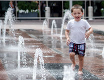 Little boy happily Playing in water at Union Station. A little boy runs through the water in the new public Union station fountains, located in  down town Denver Stock Photography
