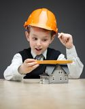 Little boy in hard hat with house model and ruler Royalty Free Stock Images