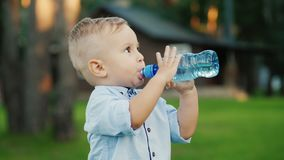 The little boy has been drinking water from the bottle for 1 year. Standing in the backyard of your house