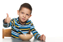 Little boy has breakfast at the table Royalty Free Stock Photos